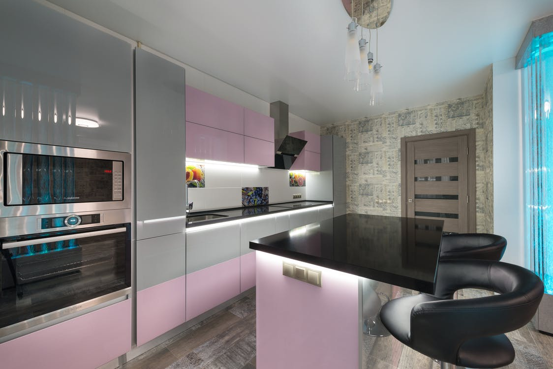 Contemporary stylish interior of kitchen with contemporary built in appliances and cabinets with luminous lights