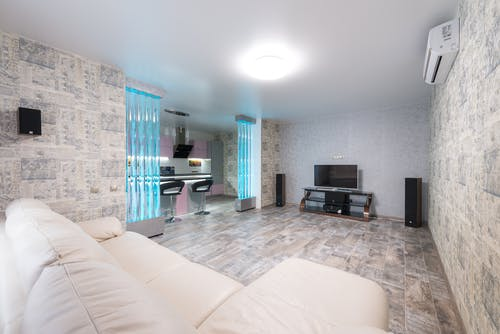Comfortable white sofa placed in spacious room with TV and decorative colorful bubble wall near modern kitchen in stylish apartment