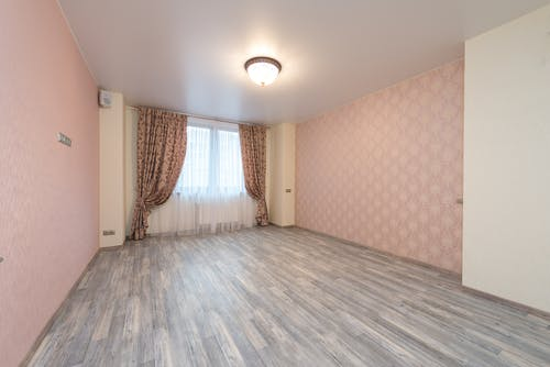 Empty spacious room with laminate and window with colorful curtains between walls with pink ornamental wallpapers and glowing white chandelier