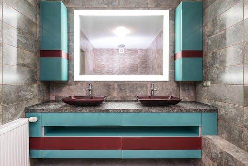 Modern sinks under illuminated mirror