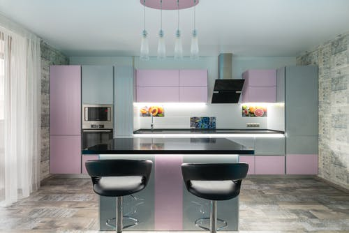 Spacious kitchen with black table and chairs placed near colorful cupboards and modern kitchenware in stylish apartment with window and tulle