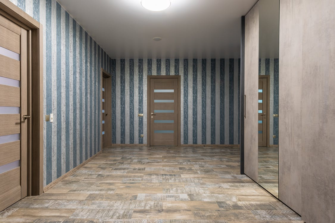 Stylish hallway with mirror on wardrobe and various wooden doors near walls with striped wallpaper in modern flat with glowing chandelier