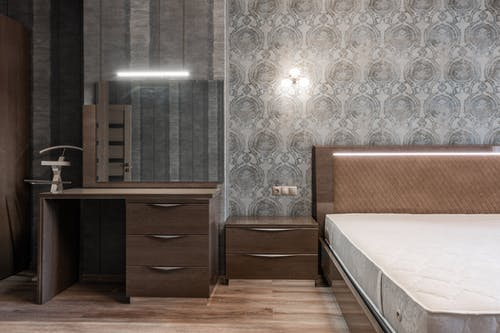Comfortable bed with white mattress placed at wall with glowing sconce wallpaper and wooden cupboard with mirror in stylish bedroom