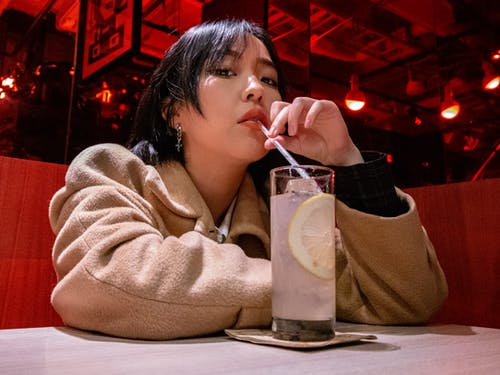 Woman in Beige Coat Drinking from Clear Drinking Glass