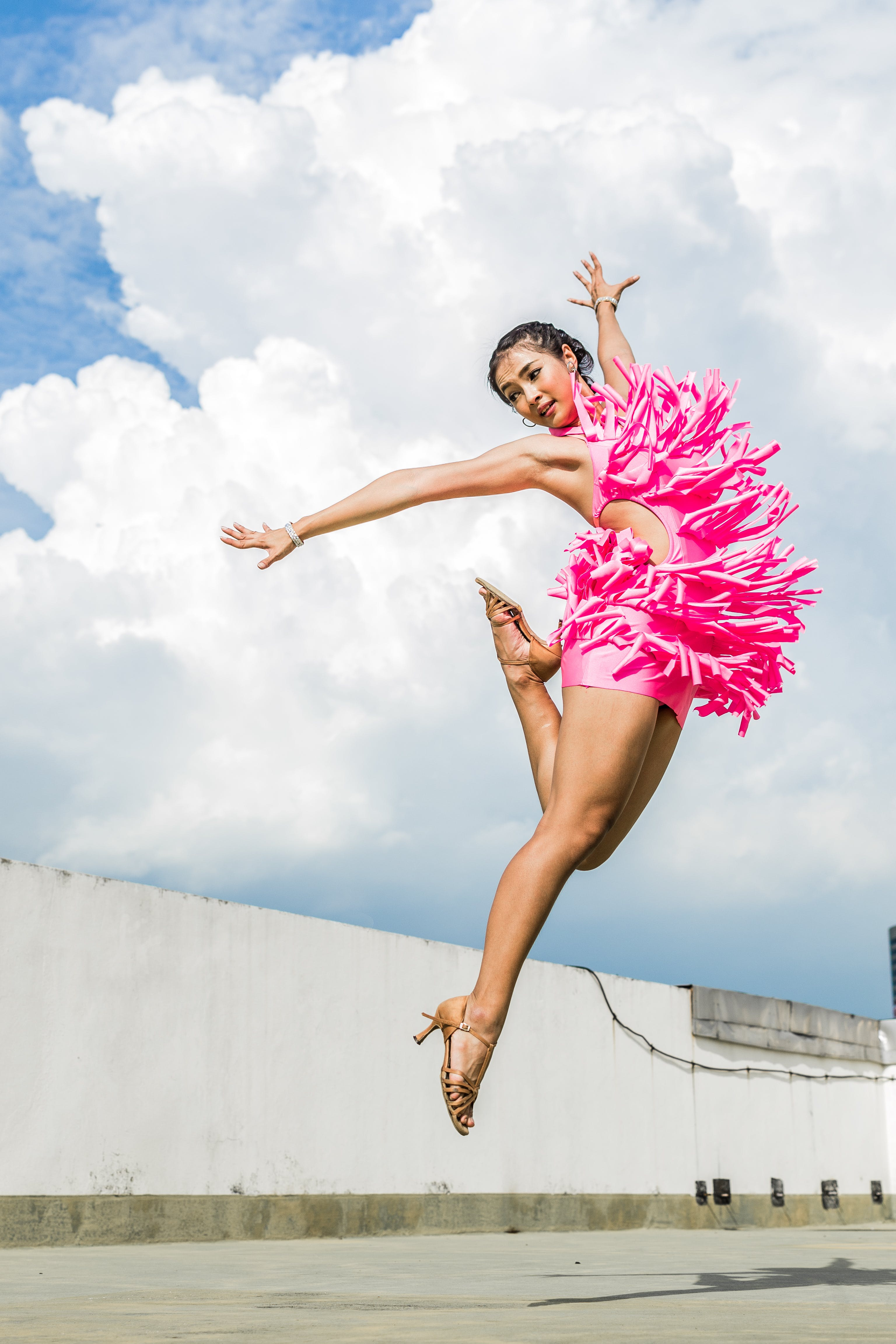 Woman in Pink Dress Doing Jump Shot While Extending Arms Under White Clouds