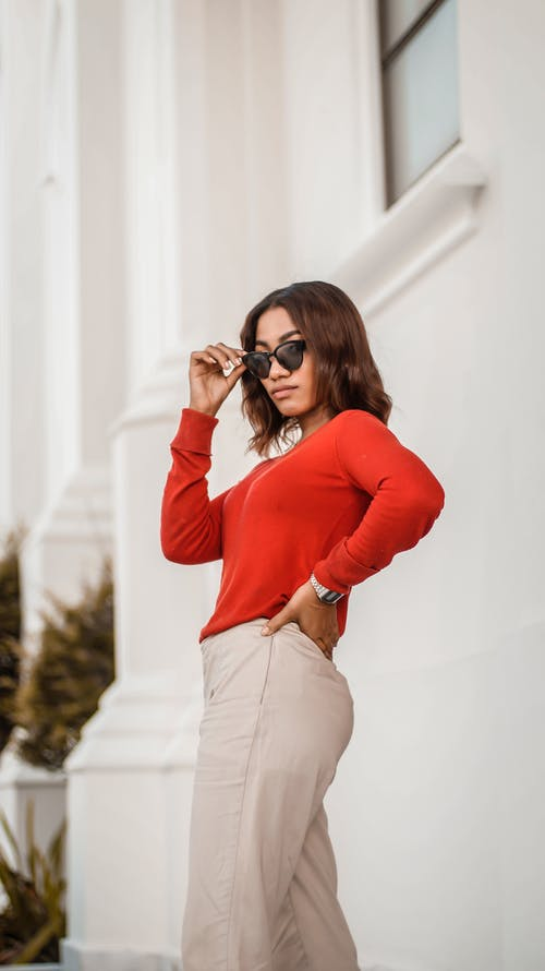 Woman in Red Long Sleeve Shirt and White Denim Jeans Wearing Black Sunglasses