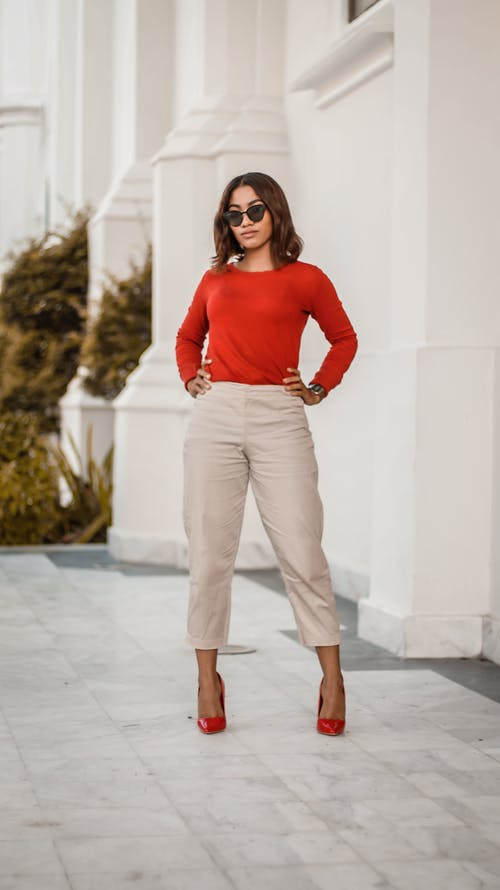 Woman in Red Long Sleeve Shirt and Brown Pants Standing Beside White Wall