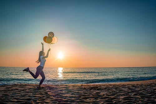 Woman in White Shirt and Black Pants Holding Balloons on Beach during Sunset