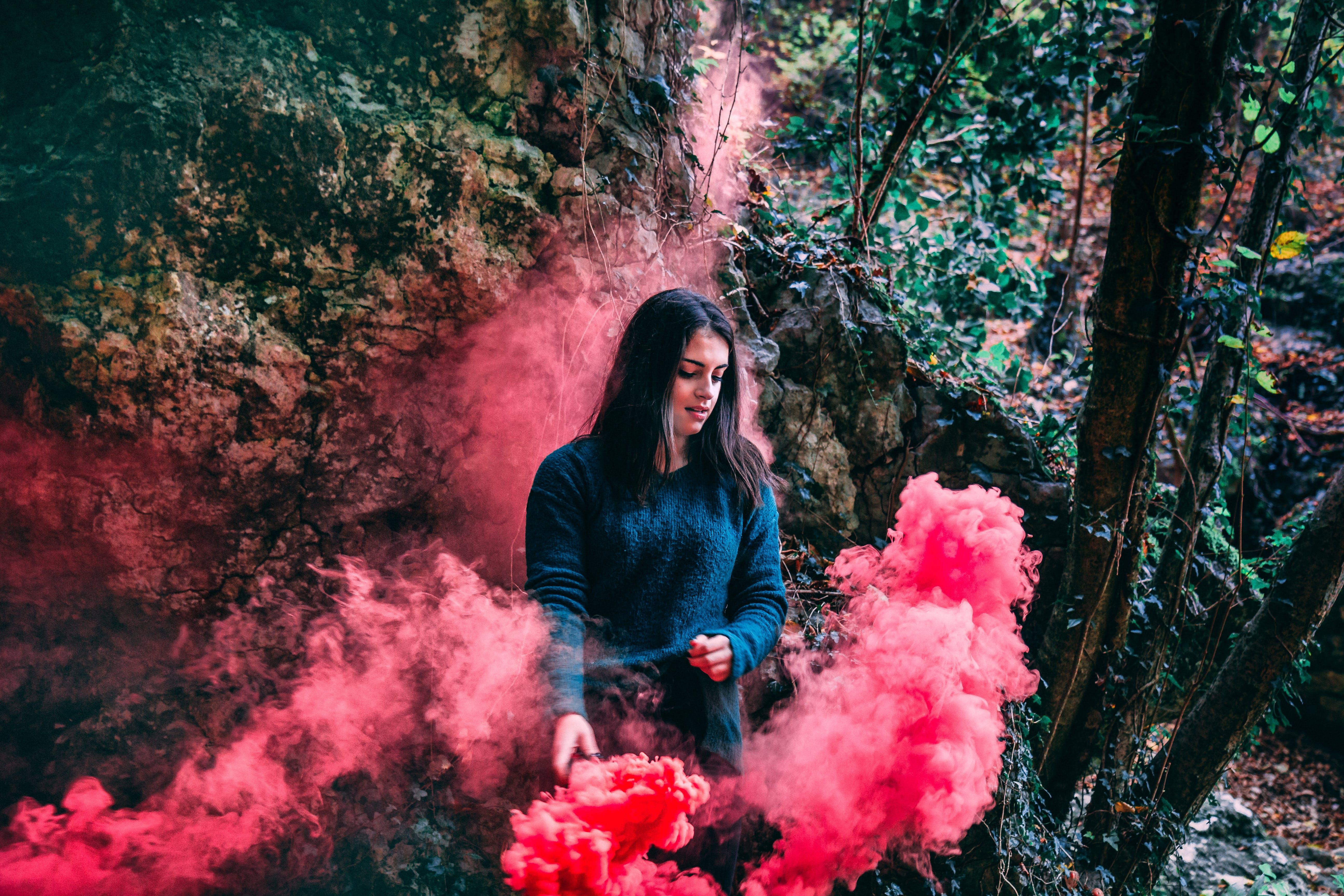 Woman Wearing Blue Long Sleeved Shirt Standing On Pink Smoke