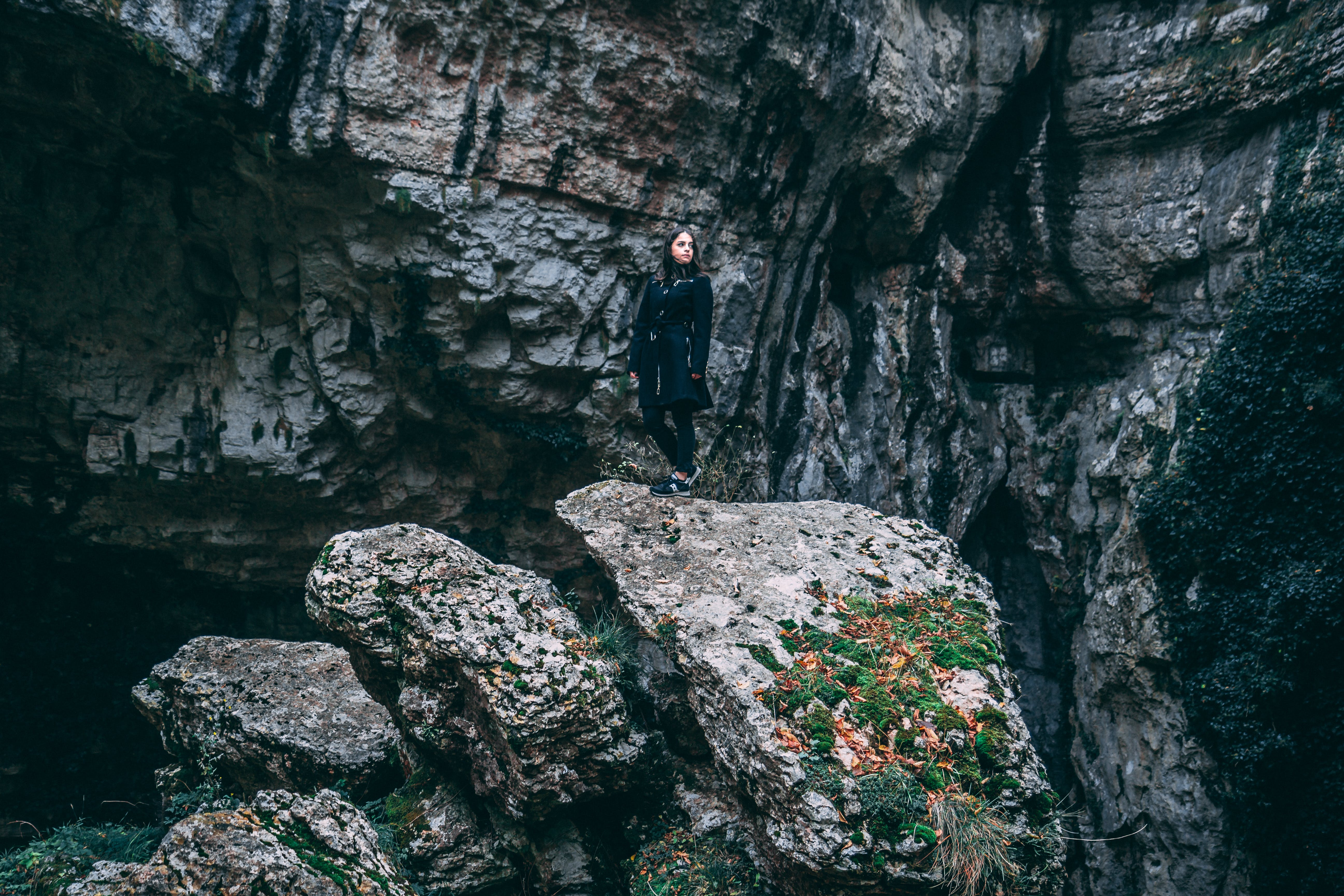 Photo of Woman In Black Outfit Standing On Rock