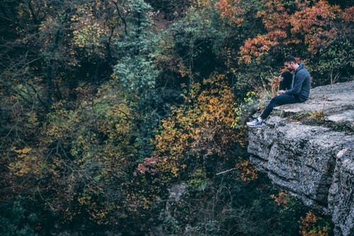 Man In Hoodie Sitting On Rock Cliff