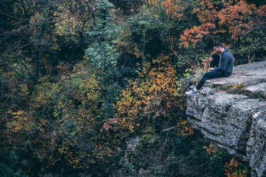Man In Hoodie Sitting On Rock Cliff