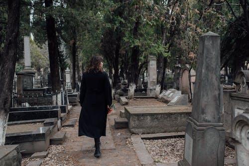 Woman in Black Dress Walking in a Cemetery