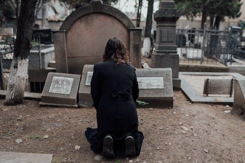 Woman in Black Dress Kneeling on Brown Soil