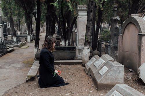 Woman in Black Dress Kneeling on the Ground