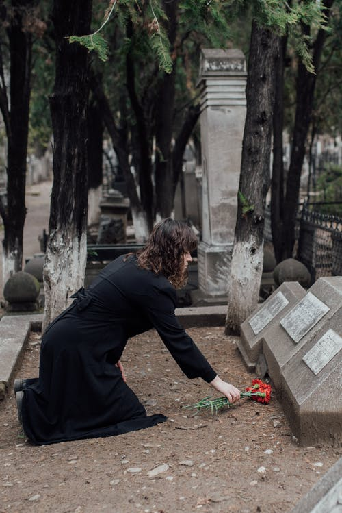 A Woman Offering Flowers On A Grave