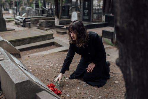Woman In Black Coat Offering Flowers In Cemetery Grave