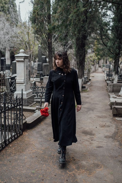 Woman Walking On Pathway Holding Flowers To Offer On A Grave