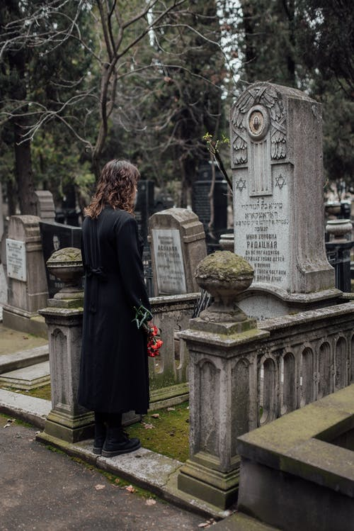 Woman in Black Coat Standing In Front Of A Tombstone With Flowers