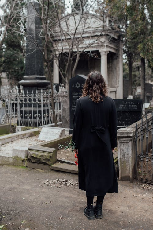 Woman Standing On Pathway Looking At A Grave From Afar