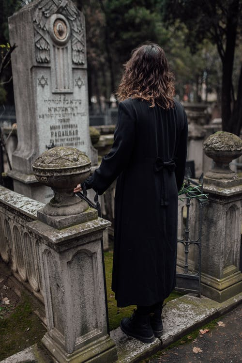 Woman in Black  Standing In Front Of A Grave