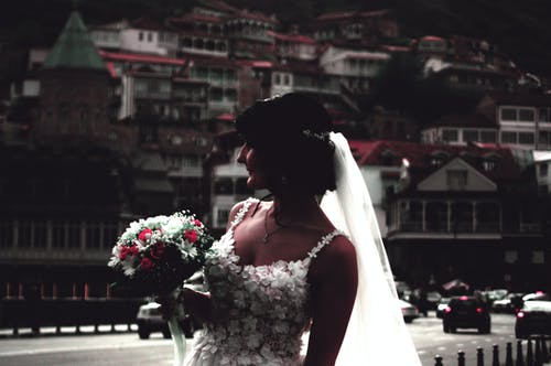 Woman in White Floral Wedding Gown Holding Bouquet of Flowers