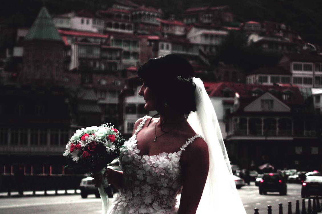 Woman Wearing White Wedding Gown Holding Flower Bouquet
