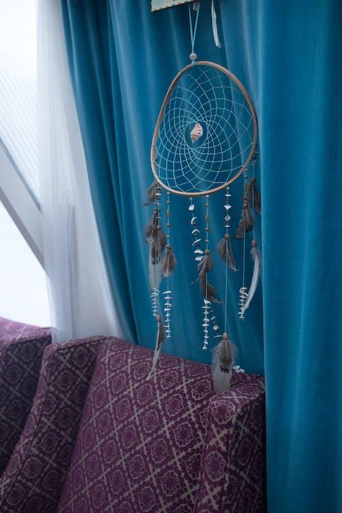 Hanging Dreamcatcher beside Blue Curtain