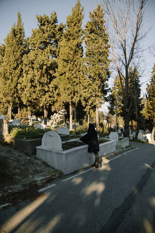 Back view of unrecognizable female in black clothes standing near stone grave in cemetery among green trees in sunny day
