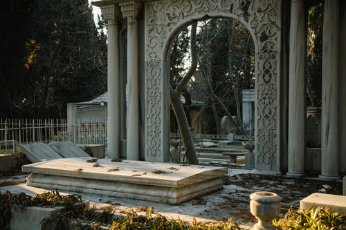 Old stone graves with ornamental sculptures placed in cemetery among green trees in sunny day