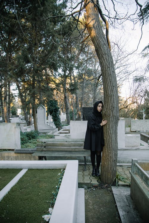 Upset woman in black outfit standing in cemetery