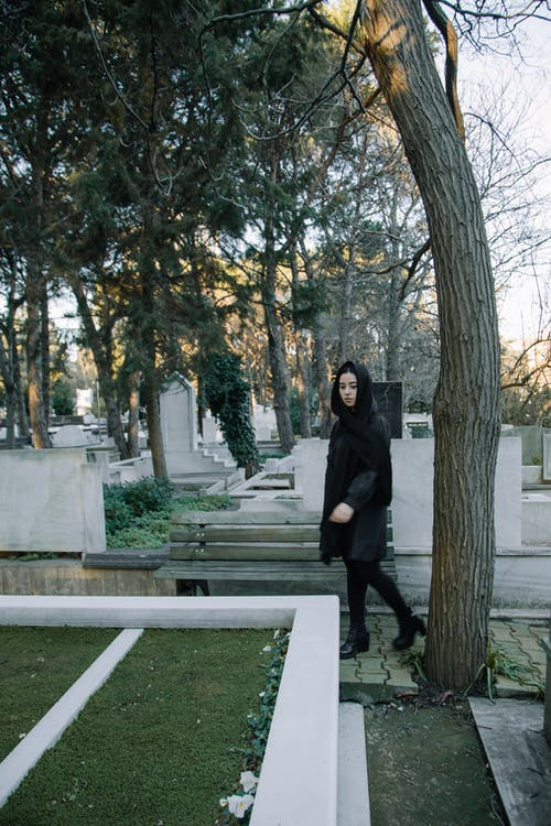 Full body of melancholy woman in black clothes and headscarf walking in cemetery among green trees in daytime