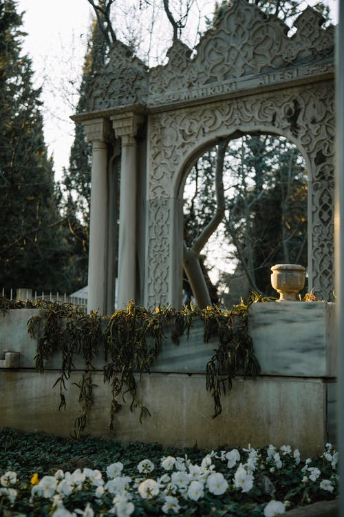 Decorative arch on grave with plants in cemetery