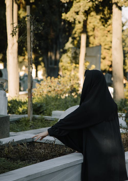 Unrecognizable sorrowful woman against grave with plants in cemetery