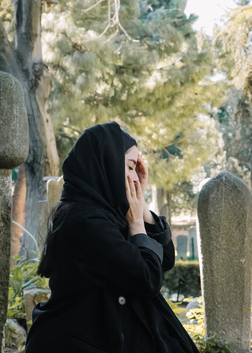 Mournful woman touching cheek against headstone in cemetery