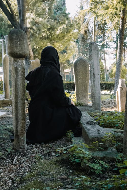 Back view of anonymous female wearing black clothes sitting near gravestone in graveyard