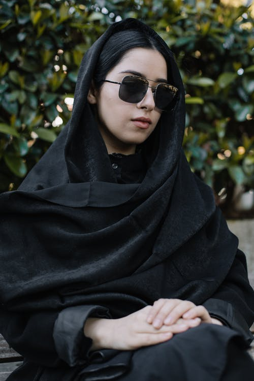 Woman in headscarf and sunglasses sitting on bench