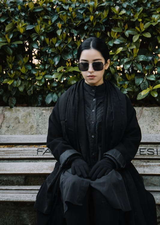 Melancholic female in black outfit and sunglasses sitting on bench and suffering from death of close person