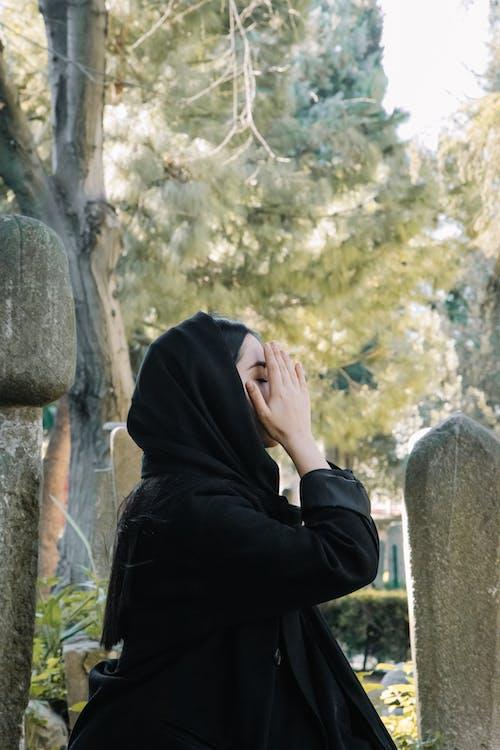 Woman in black headscarf surviving death in cemetery