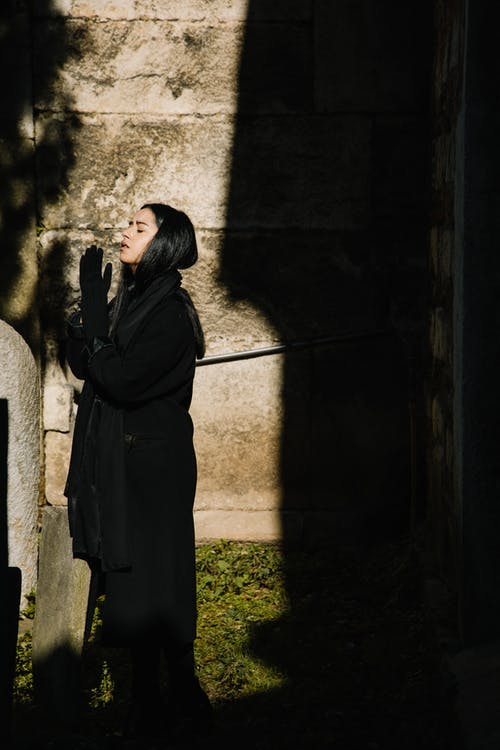 Side view of female in mourning black clothes and headscarf praying with closed eyes in cemetery