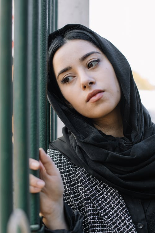 Serious woman in headscarf near fence