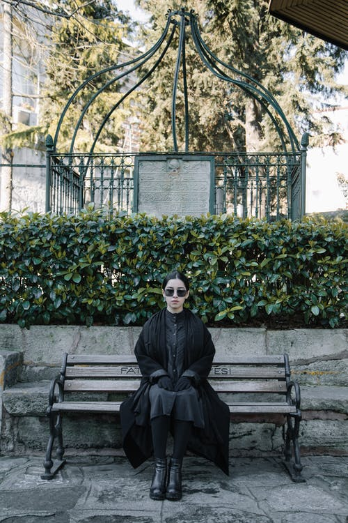 Full body of unemotional female in sunglasses sitting on bench against bushes in cemetery