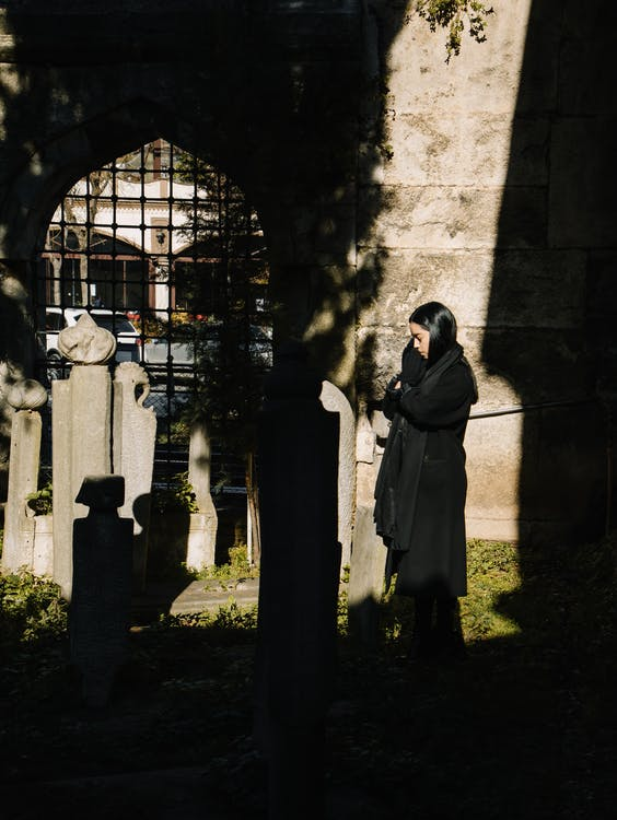 Woman praying for deceased in cemetery