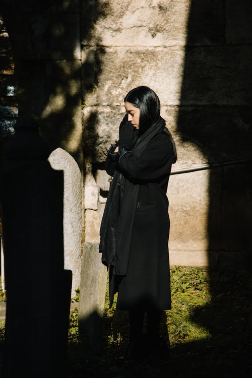 Side view full body of female in black mourning clothes standing near grave and praying with closed eyes