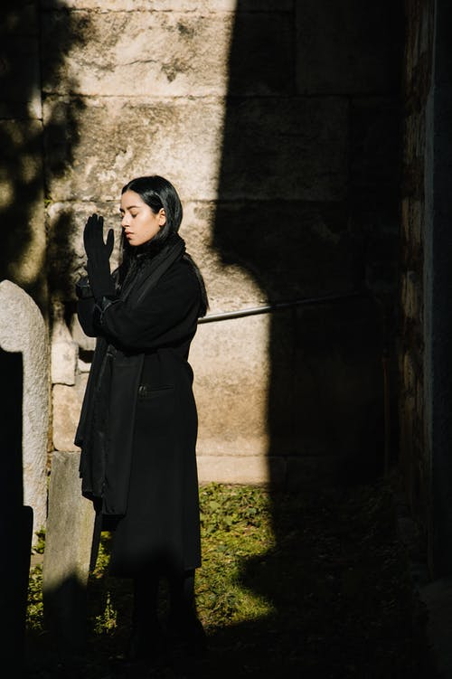 Woman in black clothes praying in Gothic cemetery