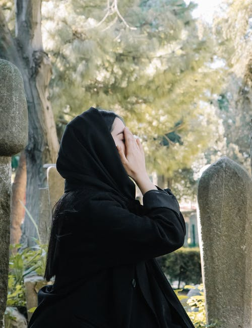 Side view of sorrowing woman in mourning clothes crying at grave of deceased in cemetery