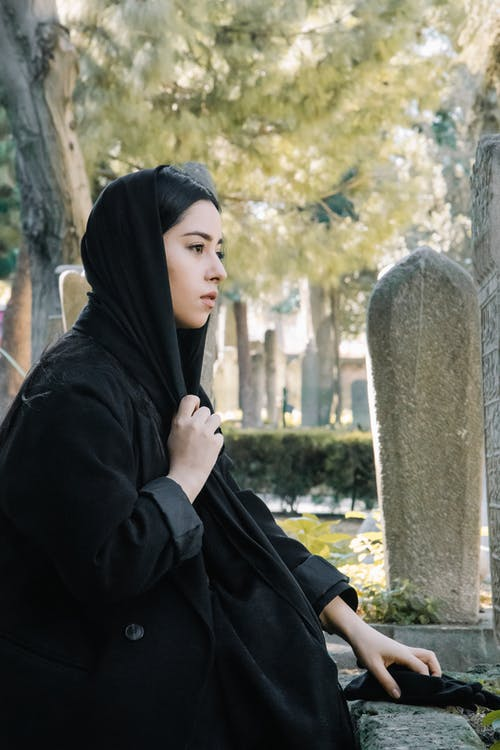 Side view of calm ethnic female wearing traditional black clothes and headwear sitting near aged stone gravestones on obsolete cemetery