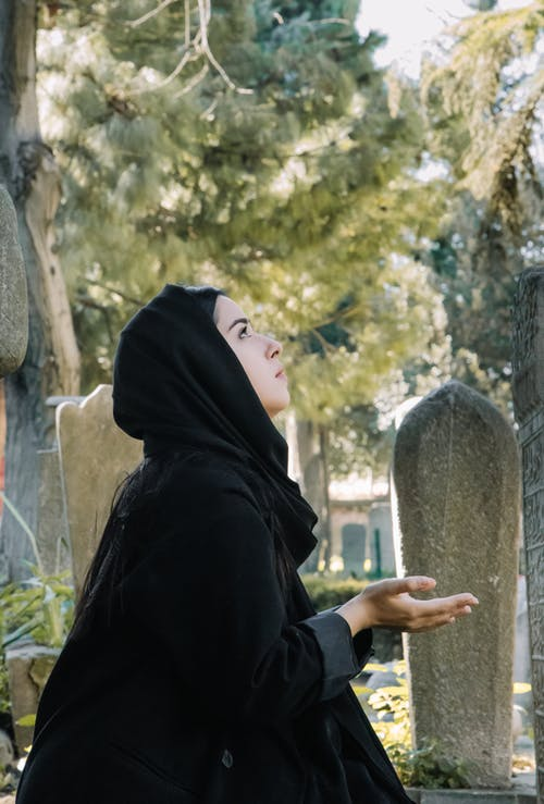 Ethnic woman praying on cemetery