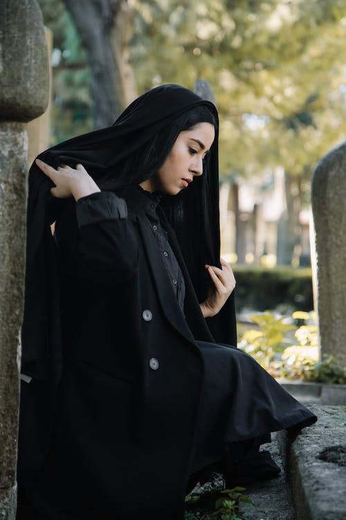 Side view of calm young ethnic female in traditional black clothes with headwear sitting near stone shabby tombstone on cemetery