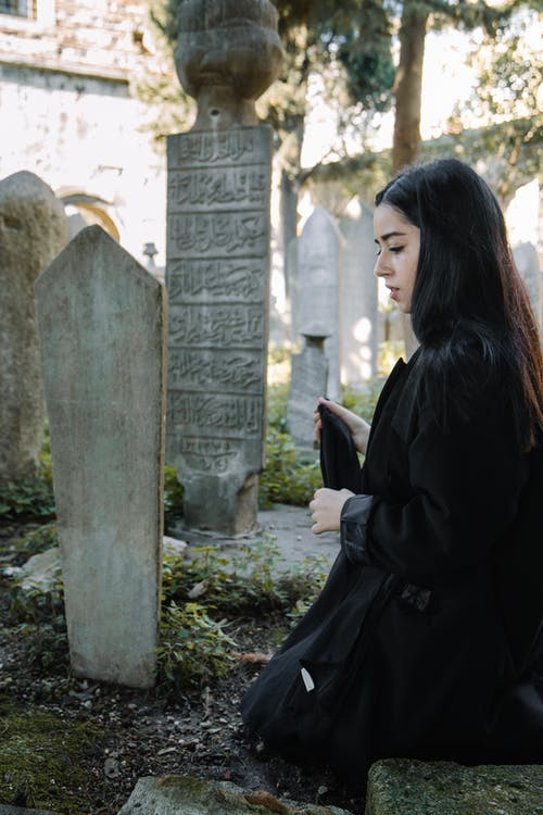 Side view of unhappy ethnic female in black clothes looking down while sitting near stone tombstone on cemetery with abundance of old graves